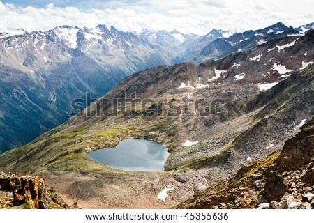 Lake in form of a heart high in the mountains. Austrian Alps - stock photo