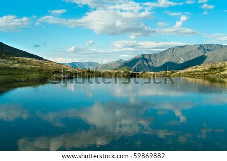 Lake in mountains and forest around it. Russian massive Khibins - stock photo
