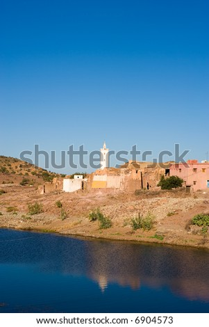 Lake in the Atlas mountain, Morocco, behind a mosque - stock photo