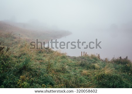 Lake in the fog, the view from the coast. soft focus - stock photo
