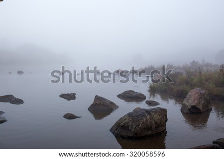 Lake in the fog, the view from the rocks - stock photo