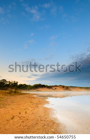 Lake in the mist with dunes and cloudy sky at sunset - stock photo
