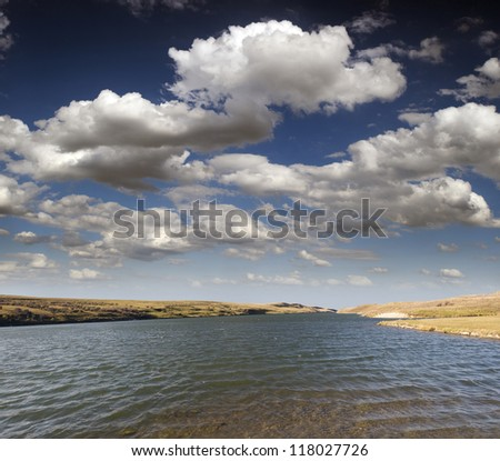 Lake - lake in Alberta's prairies with clouds and blue sky (Chain Lakes Prov.Park in Alberta, Canada) - stock photo