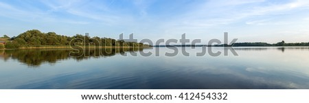 Lake landscape (panorama) with views of the distant shore. - stock photo
