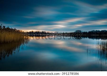 Lake landscape sunset photographed on long exposure. Polish lake in Mazury lake district. - stock photo