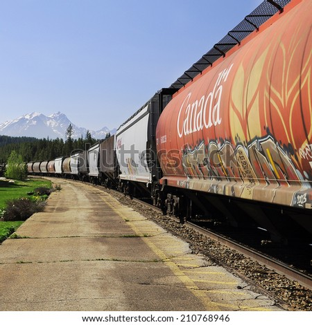 LAKE LOUISE STATION, CANADA - JUNE 09: Long freight train after famous spiral tunnels goes from Vancouver to Calgary on June 09, 2011 in Lake Louise, Canada.  - stock photo