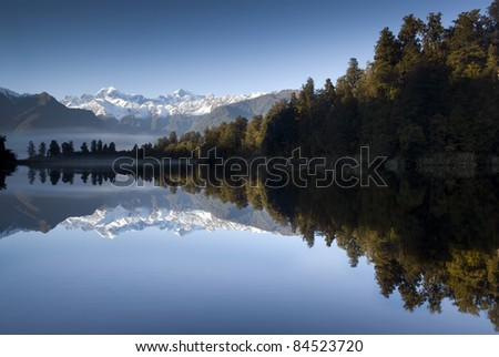Lake Matheson on a beautiful still morning with Mt Cook and Mt Tasman. South Island, New Zealand. - stock photo