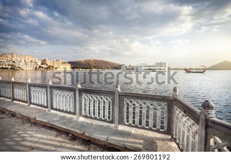 Lake Pichola with white palace in the center at cloudy sky in Udaipur, Rajasthan, India - stock photo