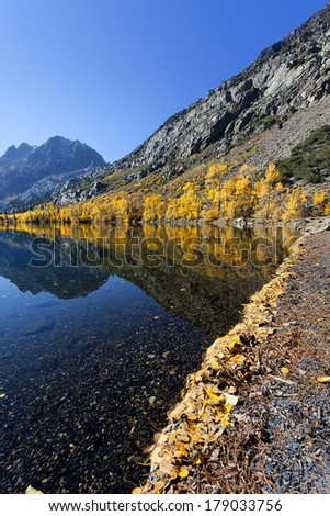 Lake Reflection of yellow Autumn colors and rugged mountains, Silver Lake, June Lake Loop, Sierra Nevada Range, California - stock photo
