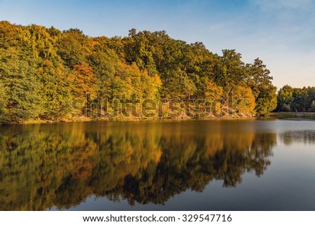 Lake reflections of fall foliage. Colorful autumn foliage casts its reflection on the calm waters - stock photo