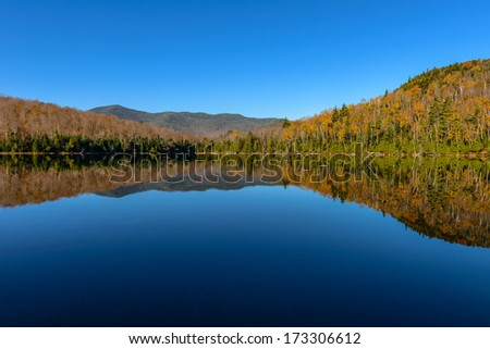 Lake Reflections of fall foliage. Colorful autumn leaves shed reflected on the calm waters of Heart Lake in Lake Placid - stock photo