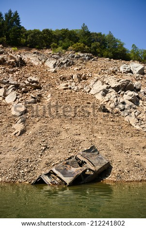 Lake Shasta, California, August 19, 2014 -- California's lingering drought exposes an abandoned car. The state's largest reservoir is receding at an average of 4.9 inches per day. - stock photo