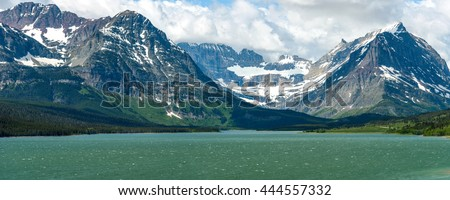 Lake Sherburne - A spring view of high mountains at shore of Lake Sherburne in Many Glacier region of Glacier National Park, Montana, USA. - stock photo