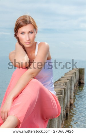 lake sitting female looking camera - stock photo
