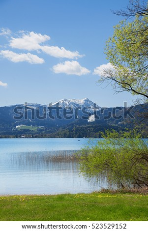 lake tegernsee at springtime, view to snow covered hirschberg mountain, bavaria