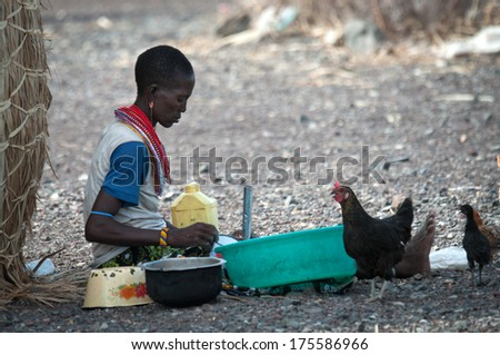 LAKE TURKANA, KENYA-JANUARY 12: Unidentified El molo woman makes rural work January 12, 2013 near lake Turkana, Kenya. The El molo are one of the disappearing tribes of Africa - stock photo