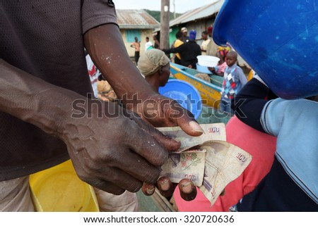 LAKE VICTORIA - KENYA - DECEMBER 24, 2014: Unidentified fisherman counting money and trading fish on December 24, 2014 in a traditional fishing village at Lake Victoria, Kenya - stock photo