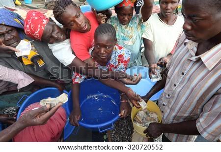 LAKE VICTORIA - KENYA - DECEMBER 24, 2014: Unidentified fishermen and market women trading fish on December 24, 2014 in a traditional fishing village at Lake Victoria, Kenya - stock photo