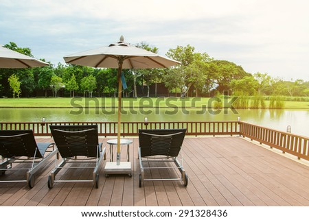 Lake view in summer with relaxation seat and umbrella in wooden terrace