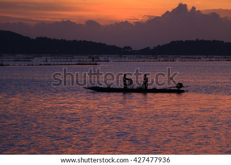 Lake view with fisherman on colorful boat in morning time  - stock photo