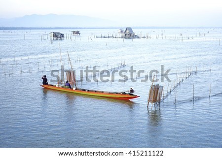 Lake view with fisherman on little colorful boat in morning time:select focus with shallow depth of field. - stock photo