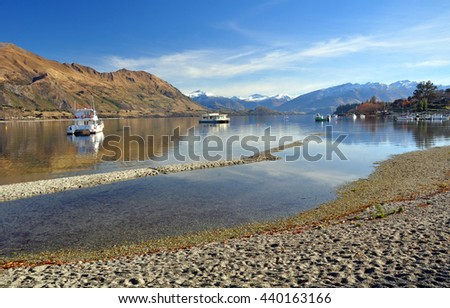 Lake Wanaka and boats with the Southern Alps in the background. Central Otago, New Zealand. Note how low the lake level is after one of the hotest and driest drought Summers on record.