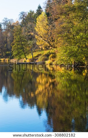 Lake with a jetty by the beach in autumn