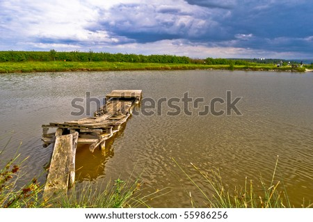 lake with small quay for fishing - stock photo