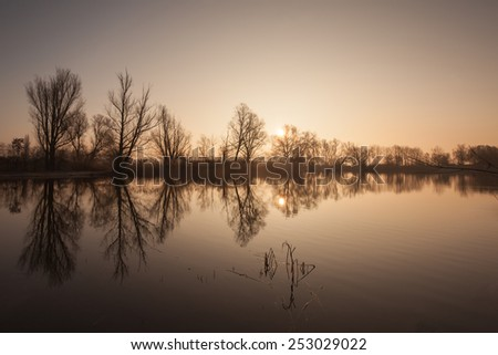 Lake with trees reflected in the water and a low positioned sun - stock photo