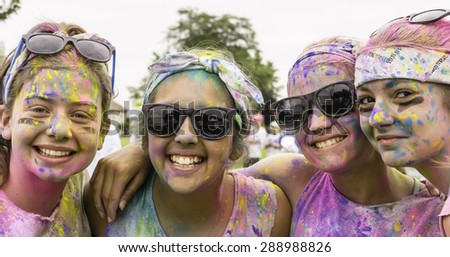"LAKE ZURICH, ILLINOIS, USA - June 20, 2015: Four teenage girls with powdered faces grin together before the 5K ""fun run"" they will start soon with many other participants in this suburb of Chicago."
