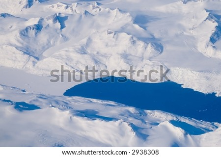 Lakes, snow, ice and mountains - an aerial view of the coast of Greenland. - stock photo
