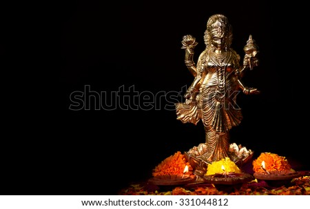 Lakshmi - Hindu goddess, Goddess Lakshmi. Clay diya lamps lit with Goddess Lakshmi during Diwali Celebration. Greetings Card Design Indian Hindu Light Festival called Diwali - stock photo