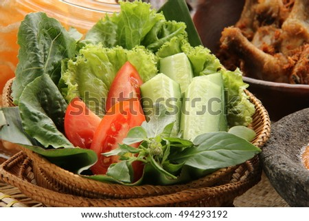 Lalapan or fresh raw vegetables basket. Lettuce, cucumber, tomato, and sweet basil served as healthy side dish to accompany Nasi Uduk Betawi.