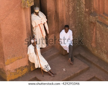 LALIBELA, ETHIOPIA, 08 JANUARY 2016: A priest and two pilgrims wearing white immaculate shawls before a side entrance to the Saint George church during the Ethiopian orthodox Christmas celebrations.