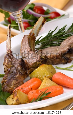 Lamb chops (ribs) with Rosemary garlic dressing, garnished with baby carrots, potatoes and rosemary sprigs. Dinner settings.
