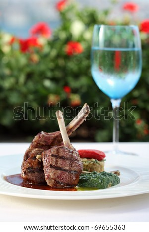 lamb chops served with risotto on a plate with glass of water - stock photo