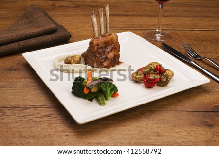 Lamb chops with mash, mushrooms, and broccoli on a square porcelain plate on a wooden table  - stock photo