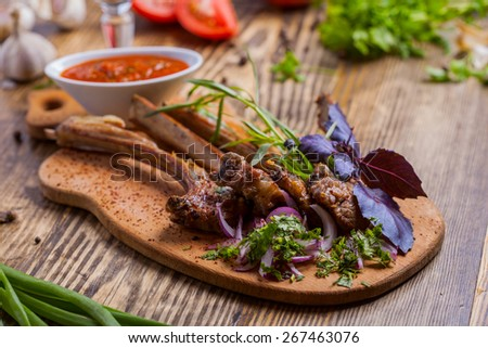 Lamb chops with sauce on wooden board - stock photo