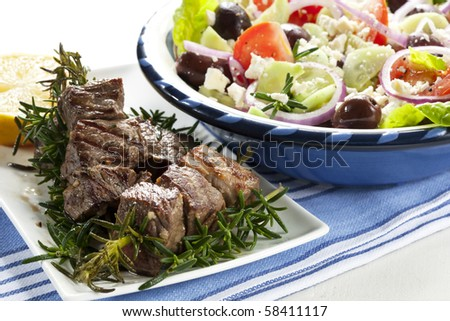 Lamb kebabs grilled on rosemary skewers, with Greek salad.  Delicious! - stock photo