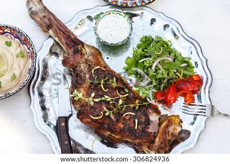 lamb leg roast on a steel plate - stock photo