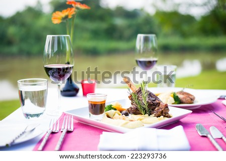 lamb shank and red wine outdoor restaurant table setting - stock photo