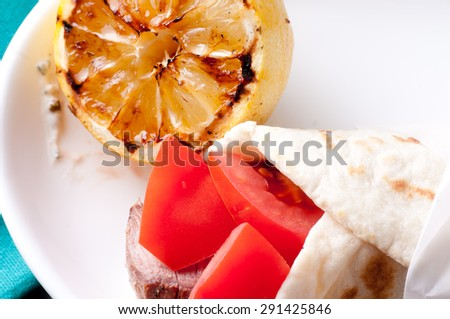 lamb skewer wrapped in flatebread with tzatziki, grilled lemon and tomato - stock photo