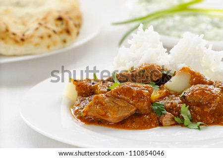 Lamb vindaloo, a spicy meat and potato curry served on rice, garnished with coriander, with naan and raita behind - stock photo