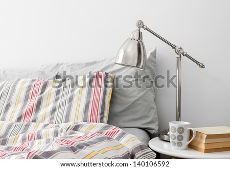Lamp and books on a side table near bed with colorful bed linen. - stock photo