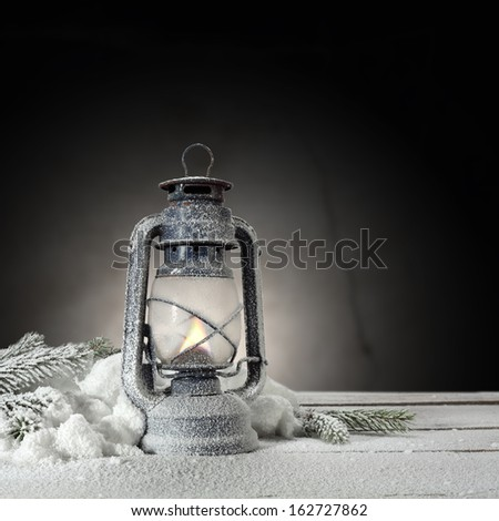 lamp and snow on desk with dark background  - stock photo