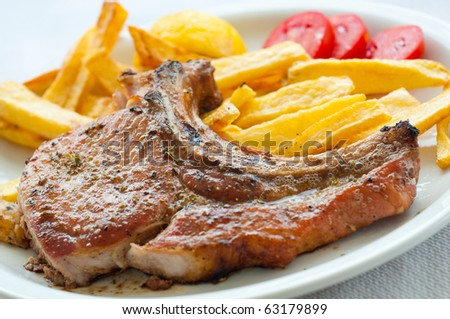 Lamp chop with french fries and tomatoes - stock photo
