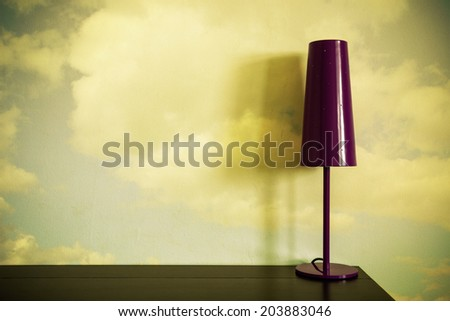 lamp on a desk with clouds on a wall - stock photo
