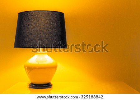 Lamp on a night table next to a bed. - stock photo