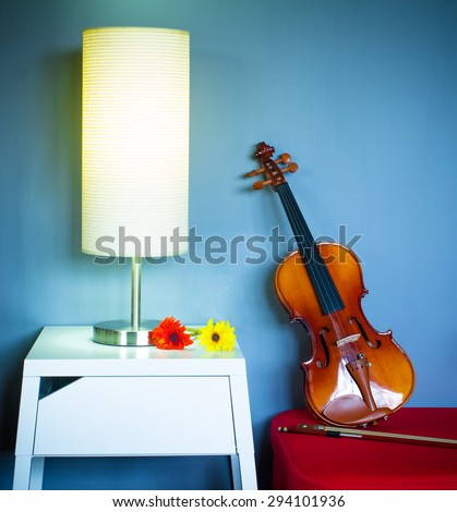 Lamp on a night table next to red seat & classical violin in living room at night for interior background - stock photo