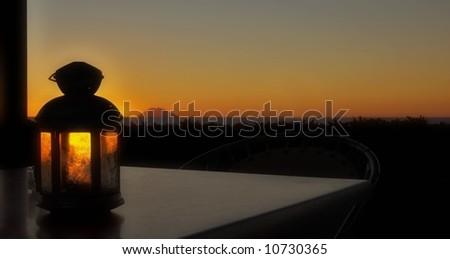 Lamp on table overlooking Sicilian Volcano island at sunset - stock photo